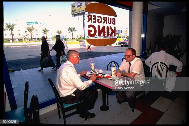Pair of British business types chatting over fare at American Burger King fast food outlet