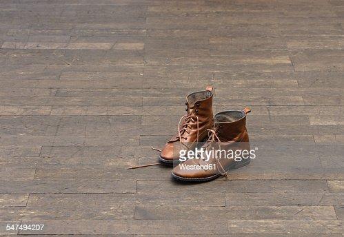 Pair of brown boots on wooden floor