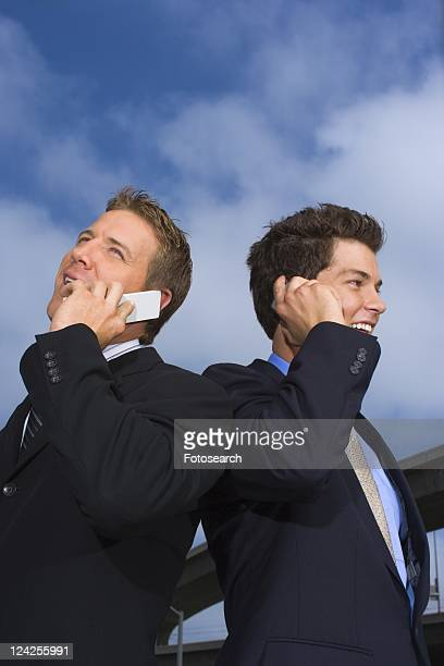 A Pair of Businessman Talking on a Cellular Phone, Waist Up, Low Angle View