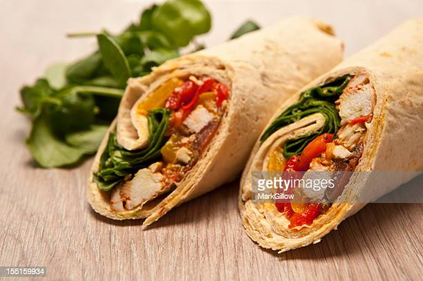 Pair of chicken and vegetable wraps on wooden table