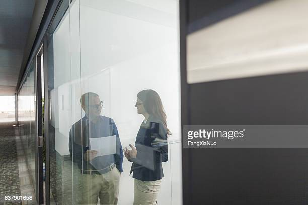 Pair of colleagues talking together in office