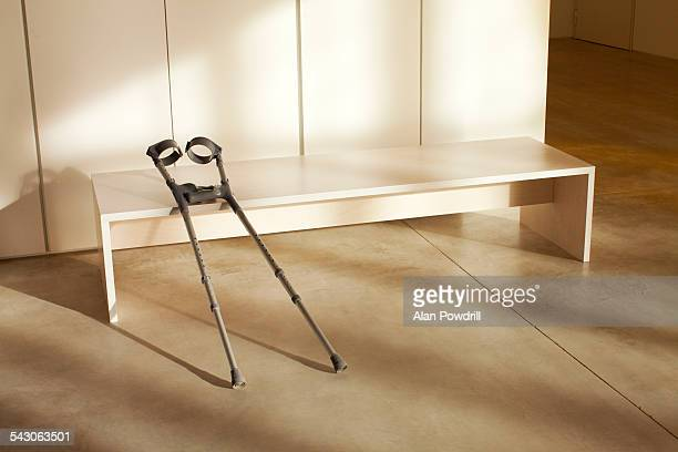 Pair of crutches leaning on indoor bench
