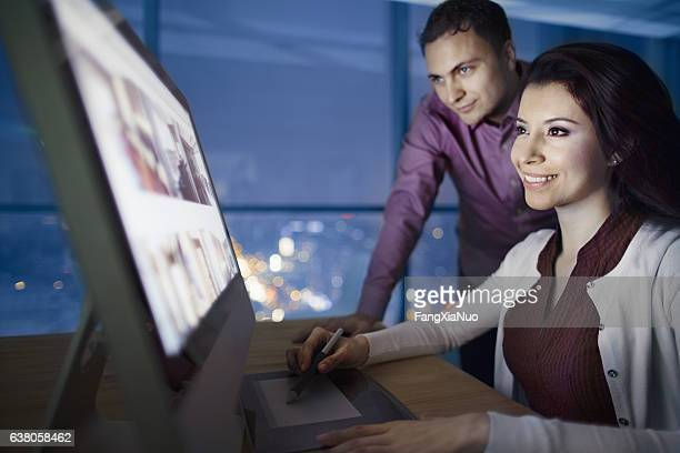 Pair of designers reviewing images on computer at night