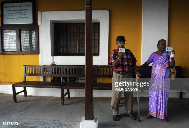 TOPSHOT A pair of elderly IndoFrench citizens display their French residential cards as they exit a polling booth in Puducherry on April 23 after...