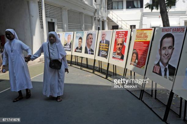 A pair of elderly IndoFrench citizens walk past at a display of portraits of French presidential candidates on the premises of a polling booth in...