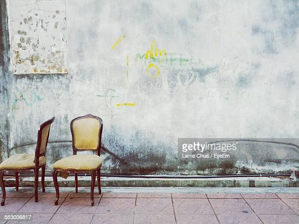 Pair Of Empty Chair Against Weathered Wall