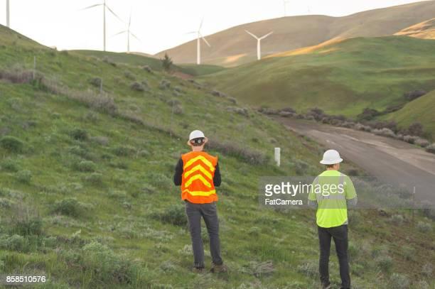 Une paire d'ingénieurs utilisent un drone pour inspecter des parcs éoliens et centrales électriques dans le pays