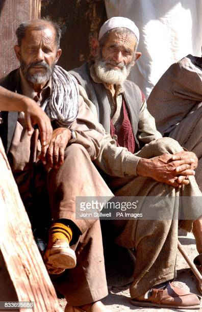 A pair of excited local men await the Prince of Wales and the Duchess of Cornwall as they tour the shattered ruins of houses in the Pakistan town of...
