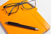 A pair of eyeglasses, a notebook and a pen on a white background: writing and reading tools for office and school