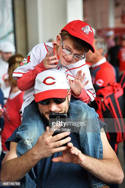 A pair of fans take a selfie as they walk to their seats before the opening day game between the Cincinnati Reds and the Pittsburgh Pirates at Great...