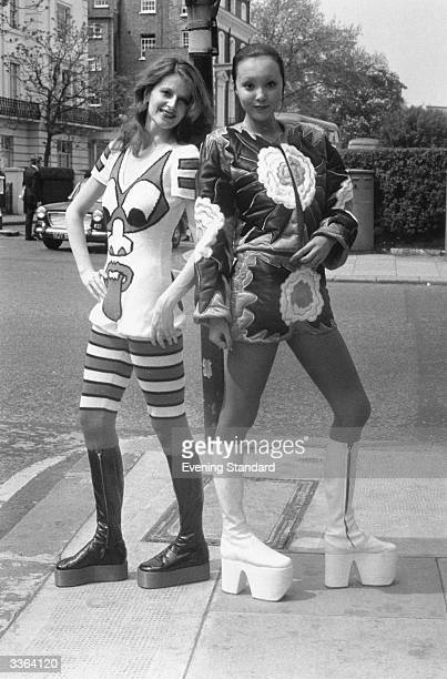 A pair of fashion models including Marie Helvin sport a couple of vibrant short suits and high boots designed by Japanese designer Kansai Yamamoto