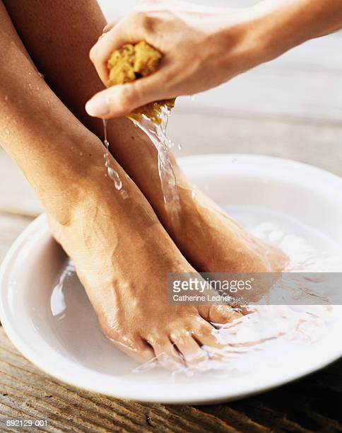 Pair of feet in bowl with water, being washed with sponge, close-up