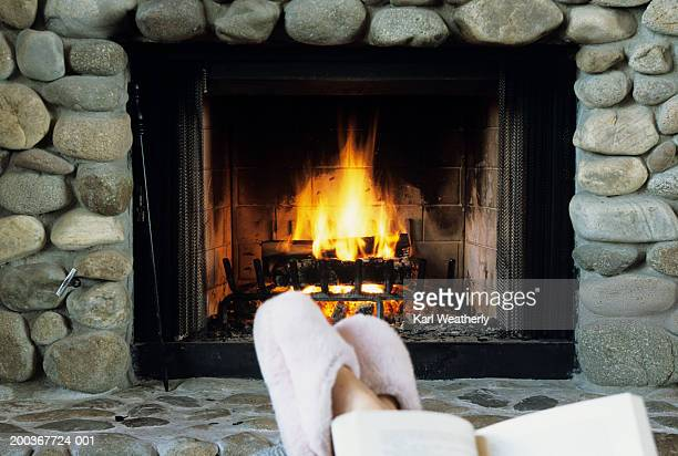 Pair of feet in slippers in front of fireplace, low section