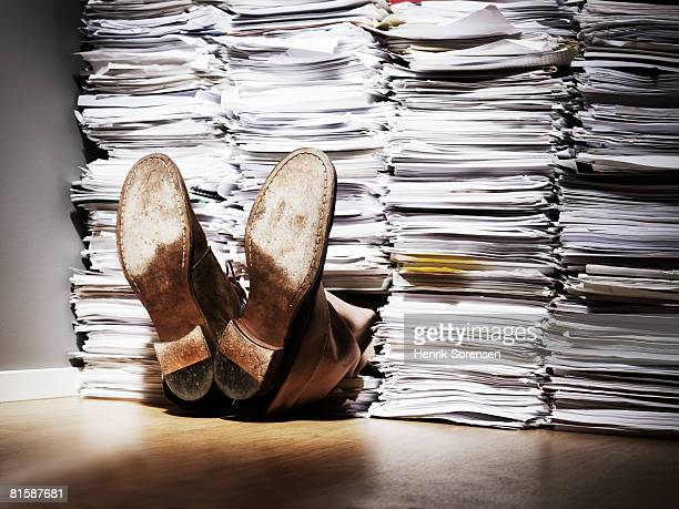 A pair of feet sticking out from under a pile of papers.