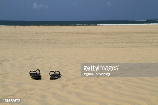 A pair of flip flops left in the sand. : Stock Photo