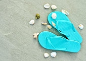 Pair of flipflops and seashells on sand beach