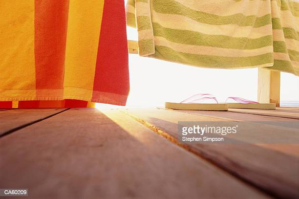 Pair of Flip-flops and towels on decking of beach house