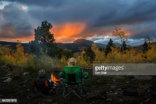 A pair of friends enjoy sunset by a campfire in Colorado
