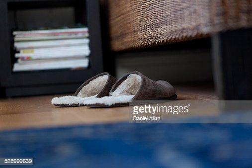 A pair of furry slippers by a bed