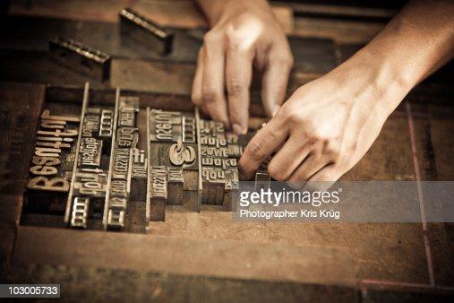 A Pair of Hands Arrange Letters for Letterpress