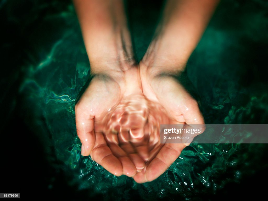 Pair of hands cupping water : Stock Photo