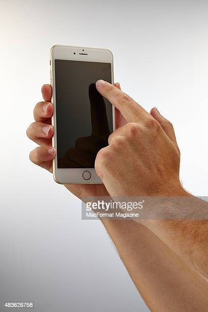 A pair of hands holding and using the touchscreen of an Apple iPhone 6 Plus taken on September 24 2014