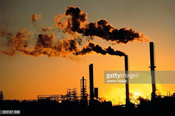 Pair of industrial chimneys emitting smoke,sunset,silhouette