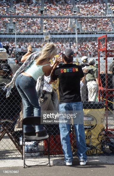 A pair of Jeff Gordon fans peer through the fence separating the infield from pit road during the running of the 2005 Daytona 500 on February 20 2005...