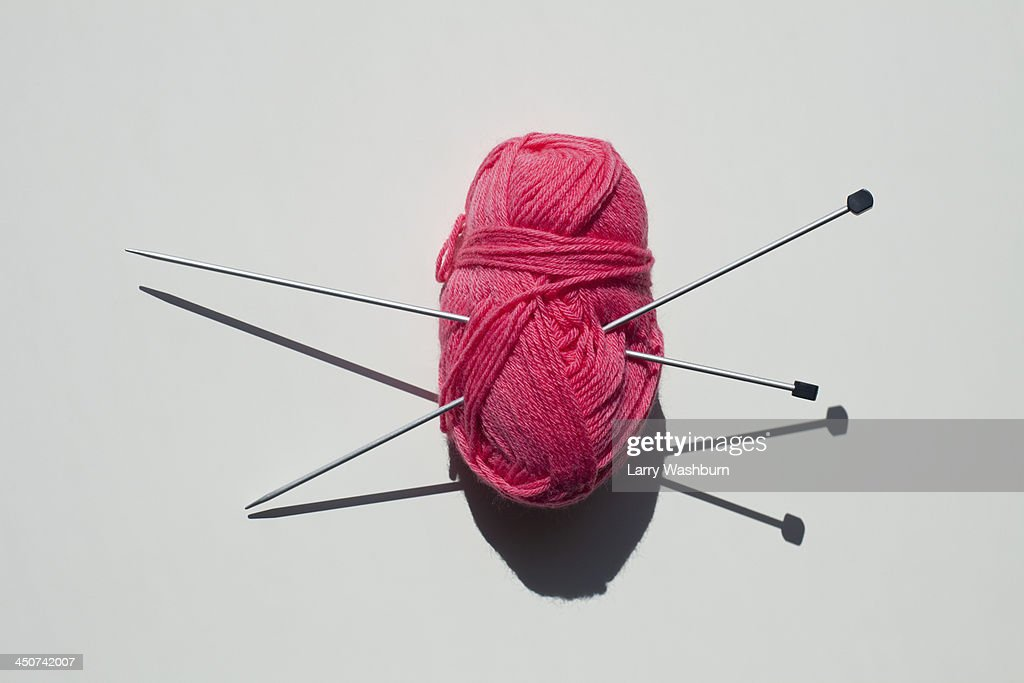 A pair of knitting needles stuck into a ball of yarn