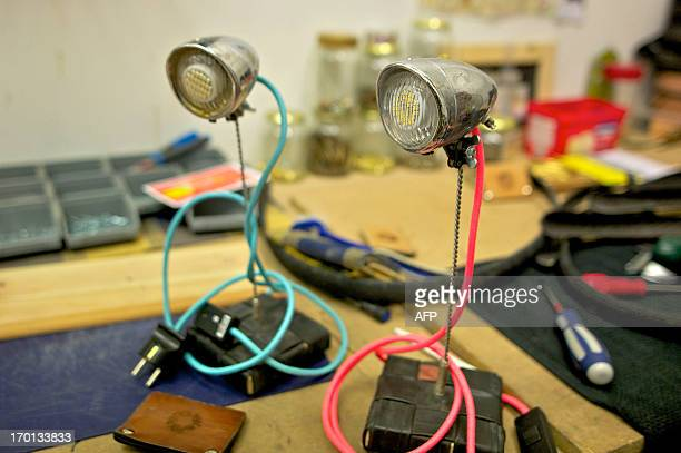 A pair of lamps made with bicycle parts are on show at the workshop of Upcycle on May 17 2013 in Delft Two Dutch entrepreneurs have found a novel way...