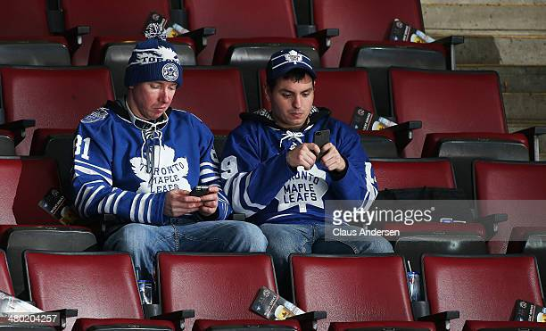 A pair of Leaf fans are busy checking there devices prior to an NHL game between the Montreal Canadiens and the Toronto Maple Leafs at the Air Canada...