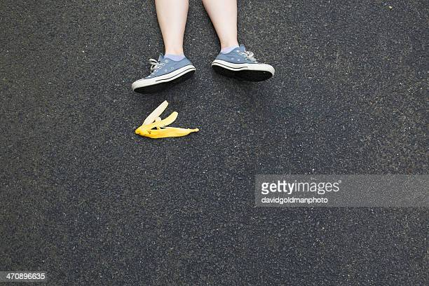 Pair of legs and banana skin on tarmac