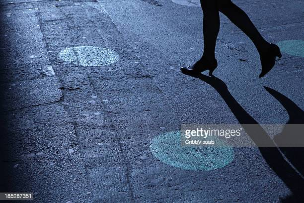 A pair of legs in heels walking on a street at night