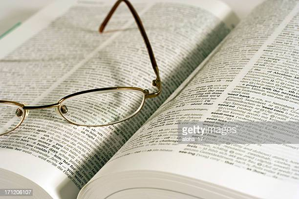 Pair of lightweight eyeglasses sitting on an open dictionary