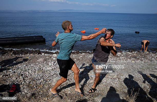 A pair of local scavengers fight over the motor of a boat that carried migrants across the Mediterranean Sea arriving on the shore of Skala Sykamnia...
