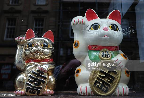 A pair of lucky cats look out form a shop window as the Chinese community come together to welcome in the Chinese New Year on February 22 2015 in...