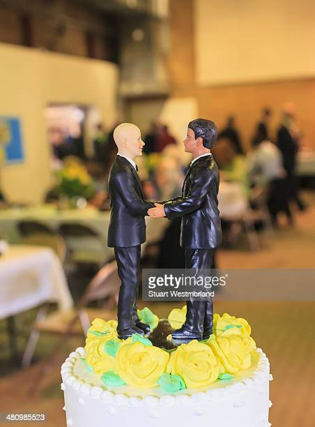Pair of male figurines on top of wedding cake at reception