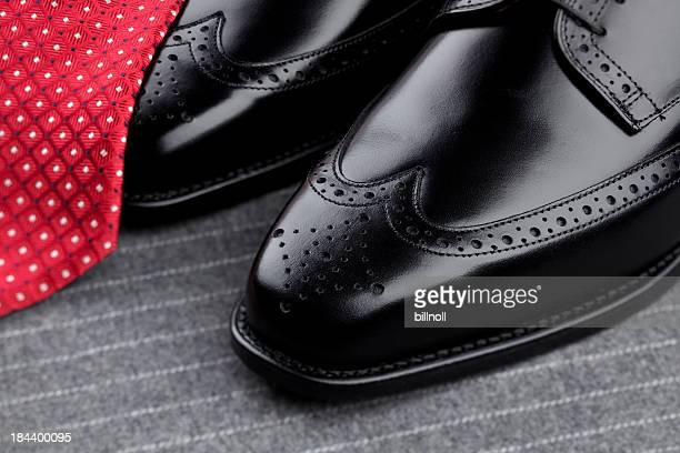 Pair of mens black shoes and red tie