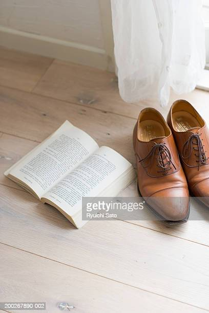 Pair of men's shoes and open book on wooden floor, elevated view
