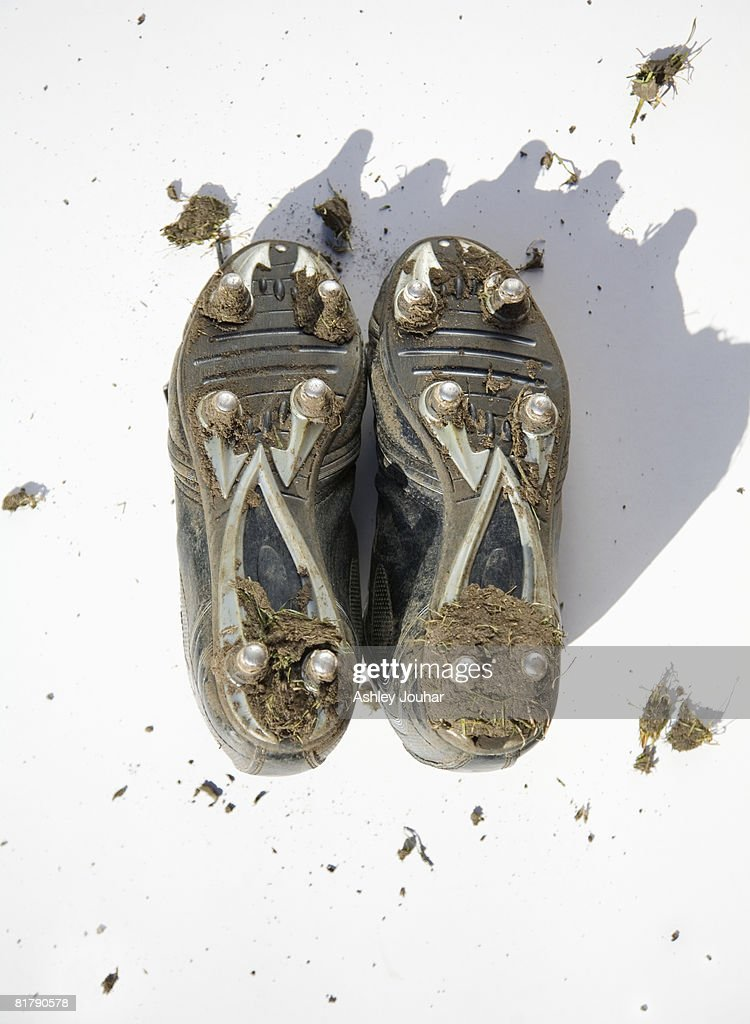 Pair of muddy football boots - studs showing : Stock Photo