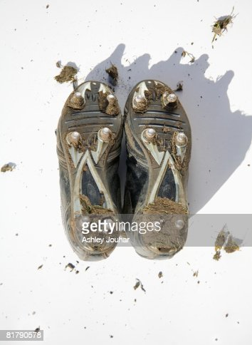 Pair of muddy football boots - studs showing