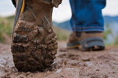 Close up of underside of a man's muddy hiking boot while hiking a trail in mountains.