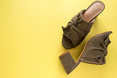 Pair of mules/clogs (military green color) on fresh yellow background, space for text