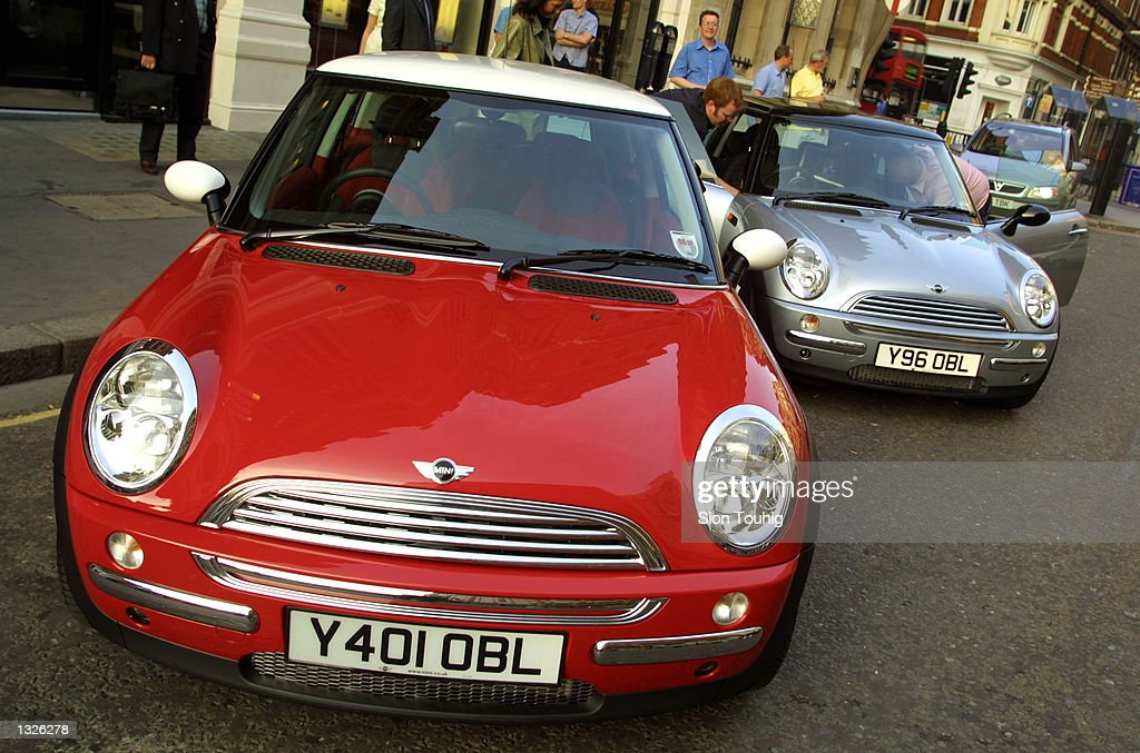 a pair of new mini cooper cars is unveiled to the auto industry press june 25