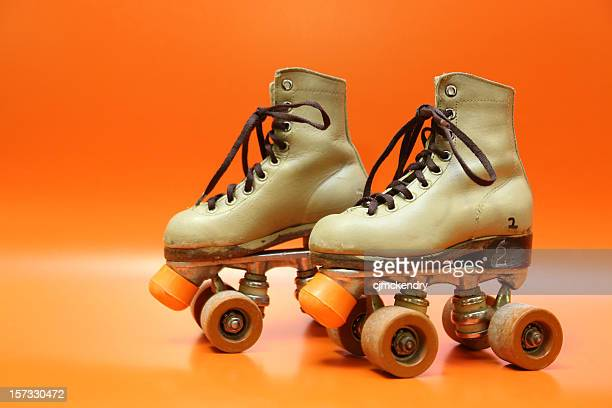Pair of orange and brown four-wheel rollerblades with laces