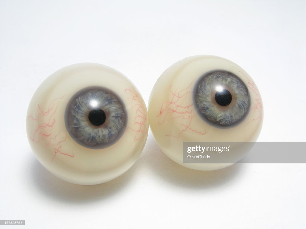 A pair of plastic eyeballs sitting on a white background