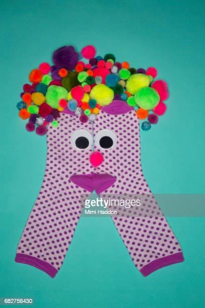 Pair of Polka Dot Socks with Googly Eyes Smiling at Camera