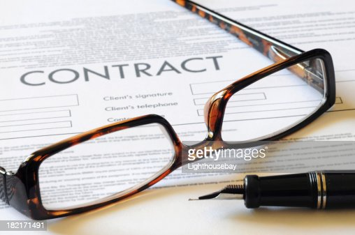 Pair of reading glasses resting on a contract with pen