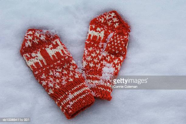 Pair of red gloves on snow