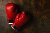 Pair of red leather boxing gloves on old table, sport and competition concept